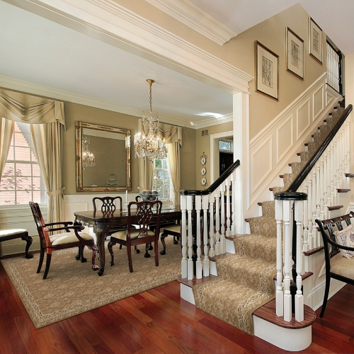 A beautiful pattern carpet runner on this staircase is complimented by the area rug in the dining room.